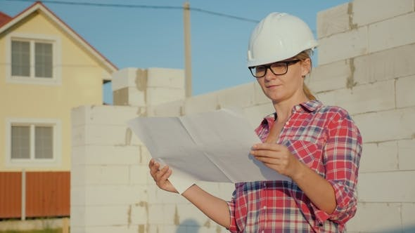 Thumbnail for Eine weibliche Ingenieurin studiert eine Zeichnung. Es steht auf der Baustelle eines kleinen Häuschens