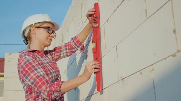 Thumbnail for A Woman Engineer Checks the Quality and Accuracy of Building a Wall in the House. Quality Control on