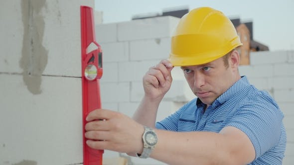 An Engineer in a Yellow Helmet Checks the Accuracy of the Construction Work