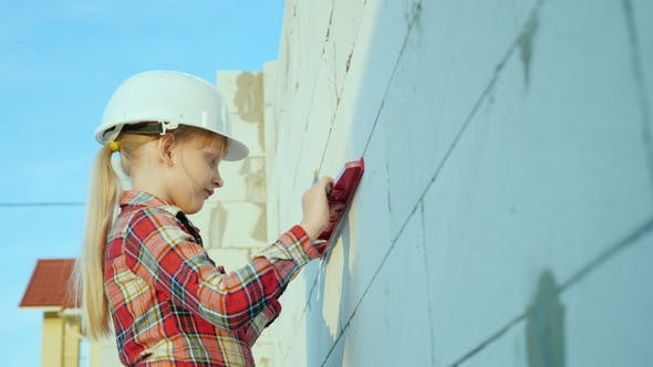 Thumbnail for A Child Engineer in a Helmet Measures the Accuracy of Wall Masonry Children's Dreams and Profession