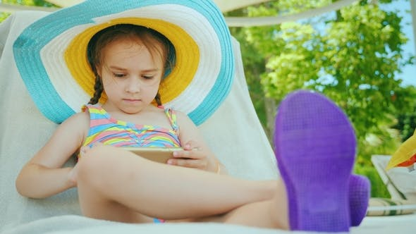 Thumbnail for Little Business Woman on Vacation. Sits in a Deckchair, Uses a Smartphone