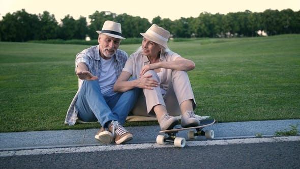 Thumbnail for Stylish Senior Couple Sitting with a Skateboard