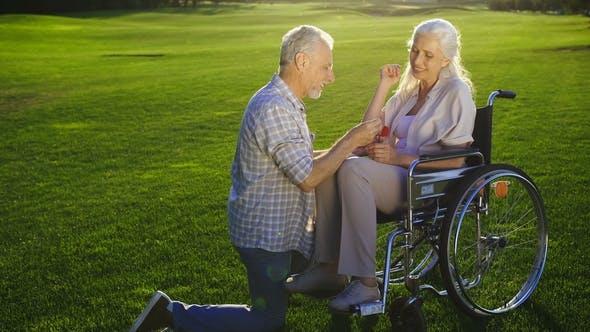 Thumbnail for Senior Man on Knee Proposing Woman on Wheelchair