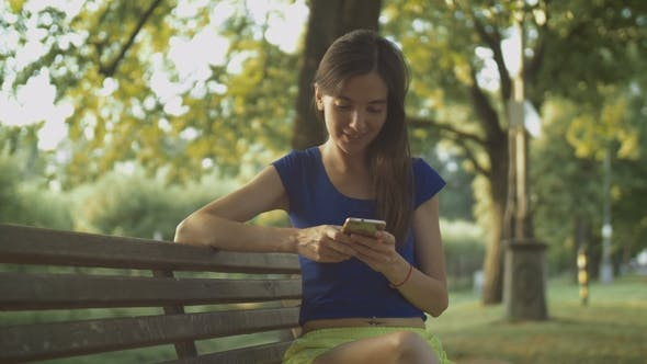 Thumbnail for Smiling Pretty Woman Texting on Cellphone in Park