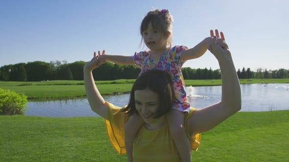 Thumbnail for Laughing Special Needs Girl on Mom's Shoulders