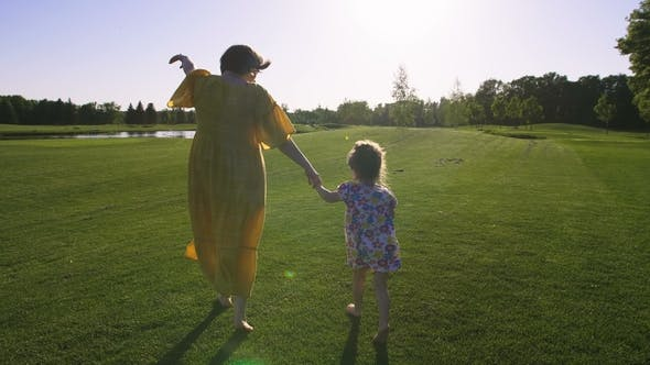 Thumbnail for Daughter and Mom Running on Green Grass Meadow