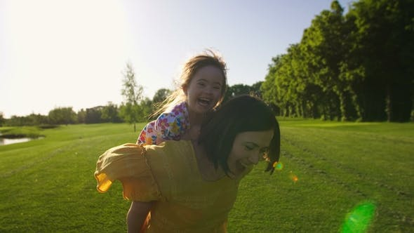 Thumbnail for Girl with Down Syndrome Riding Mother's Back
