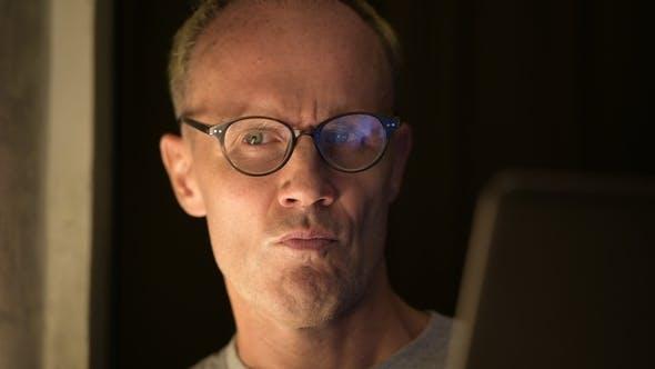 Thumbnail for Mature Scandinavian Man with Eyeglasses Thinking While Using Laptop