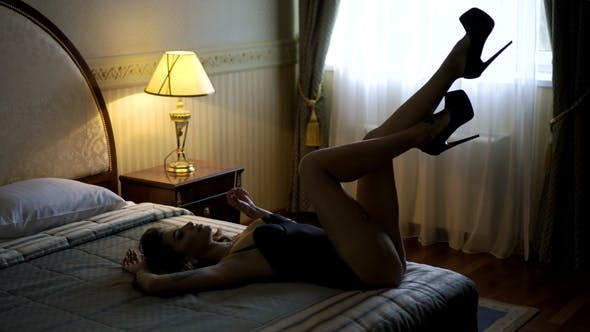 Thumbnail for Passionate Beautiful Model Lying on the Bed in the Hotel and Posing for Photos