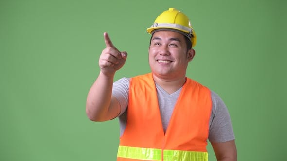 Thumbnail for Young Handsome Overweight Asian Man Construction Worker Against Green Background
