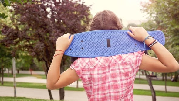 Thumbnail for Young Girl with a Skateboard on Her Shoulder Looks at the Camera