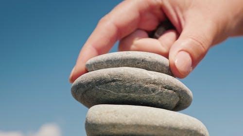 La main met la pierre dans la tour. Concept d'équilibre et  d'équilibre