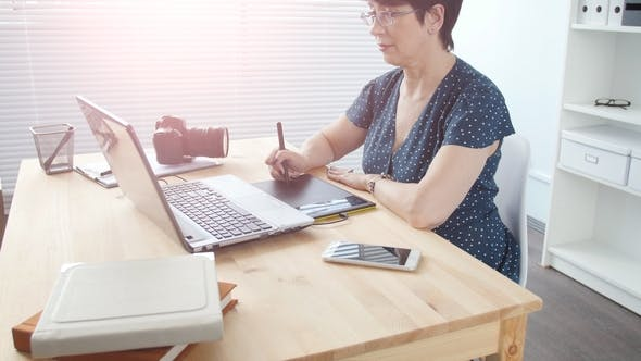 Graphic Designer Aged Woman Using Digital Graphic Tablet While Working at Modern Office