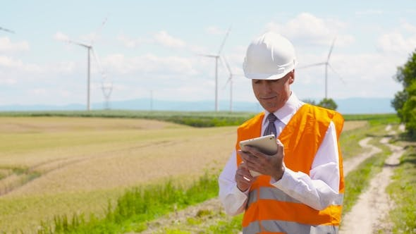 Thumbnail for Energy Engineer Working on Digital Tablet Agains Windmills Farm