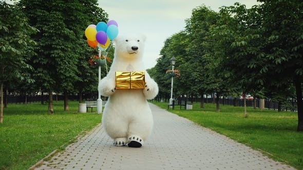 Thumbnail for A Large Polar Bear Walks Down the Street, Carries Balloons and a Box with a Gift. Birthday Gifts and