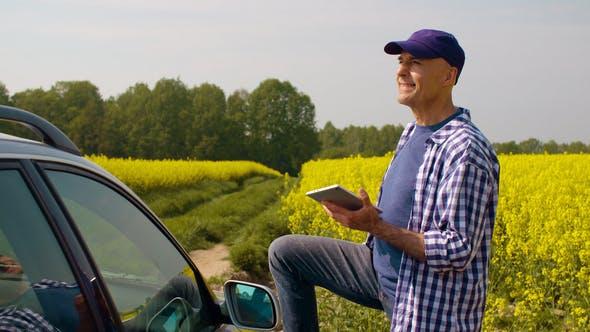 Thumbnail for Farmer Using Digital Tablet Examining Rape Blossom on Field