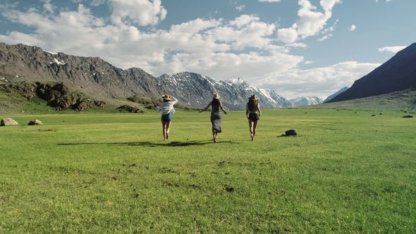 Thumbnail for Group Of Friends Hold Hands And Run Away From Camera Toward Mountain