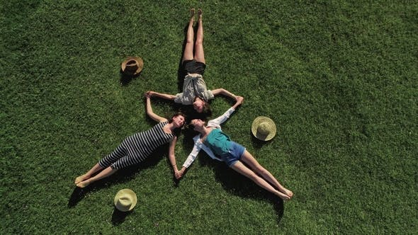 Three Attractive Girls Lying on Green Grass and Having Fun on a Meadow Sunny Day and Background of