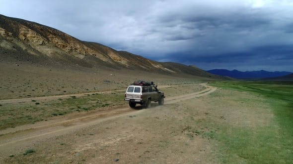 Thumbnail for Aerial View of Safari Vehicle Driving on Sand Track Road in the Altay Mountain