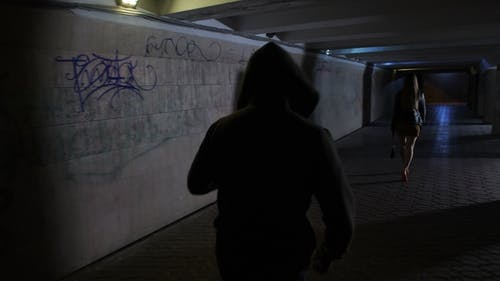 Man in Hoodie Chasing Woman in Dark Tunnel