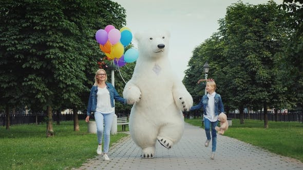Thumbnail for Mom and Daughter and a Polar Bear Are Having Fun Along the Street. Children's Holiday Concept