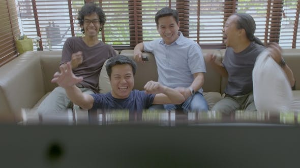 Cover Image for Group of Asian Flat Mates Watching Sports Competition on TV at Home.