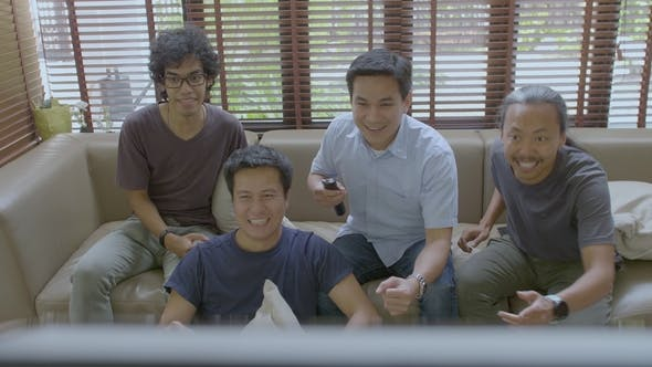 Thumbnail for Group of Asian Flat Mates Watching Sports Competition on TV at Home