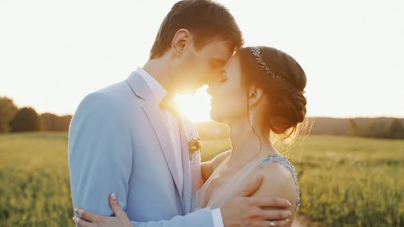 Cover Image for Bride and Groom Embrace One Another and Smile During Their Walk on a Countryside Road Sunset Light