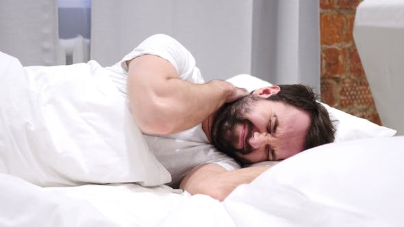 Thumbnail for Beard Man with Neck Pain Trying To Relax in Bed