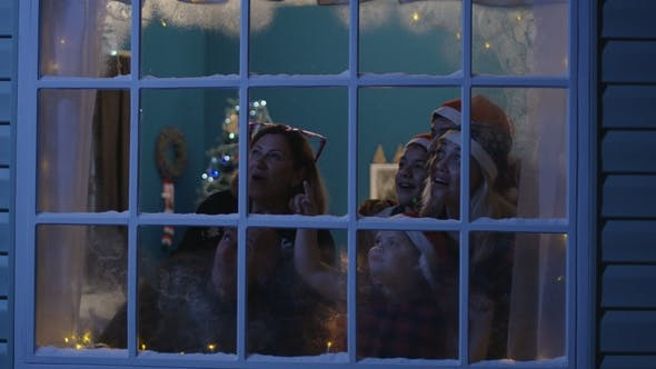 Thumbnail for Happy Family Watching Fireworks Through Window