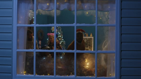 Excited Friends Looking Out in Window During Christmas