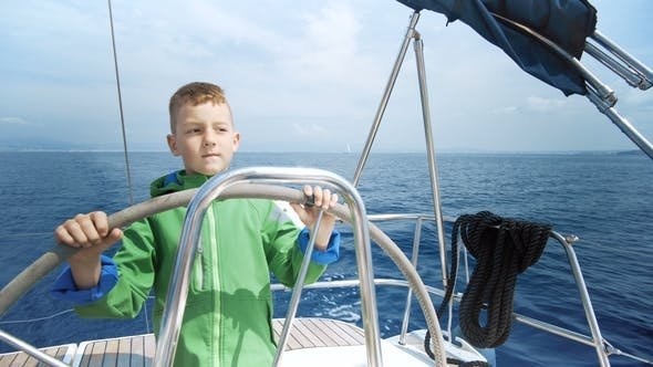Thumbnail for The Little Boy Drives a Sailing Yacht in Caribbean Sea