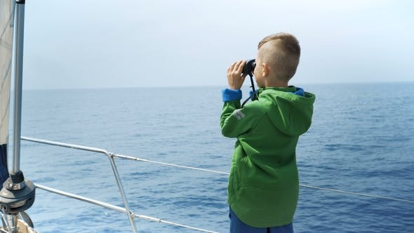 Thumbnail for Little Boy Stands on a Yacht and Looks in a Binocular