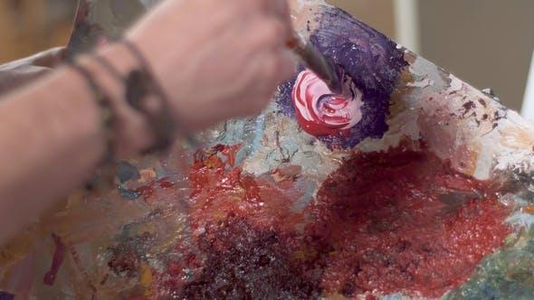 Thumbnail for Man Mixes Paints on Palette