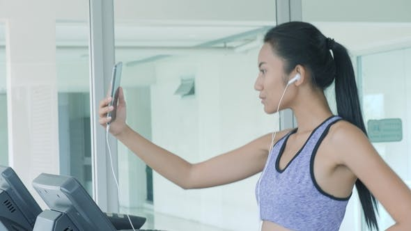 Thumbnail for Asian Girl Running on Treadmill and Talking on the Phone