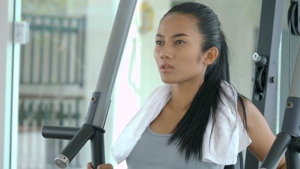 Asiatische Mädchen Body Builder mit einem Gewichte Maschine in der Turnhalle