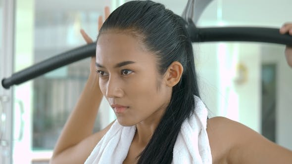 Thumbnail for Asian Girl Body Builder Using a Weights Machine in the Gym.