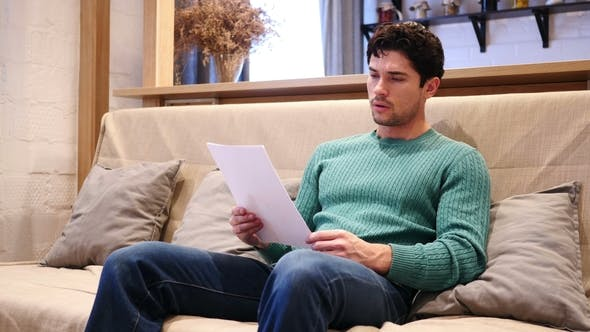 Upset Man Disappointed While Reading Documents, Paperwork