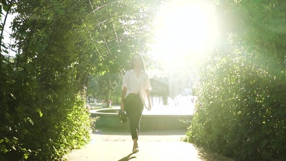 Thumbnail for Stylish Young Woman at High Heels Walking in Park at Fountains Background