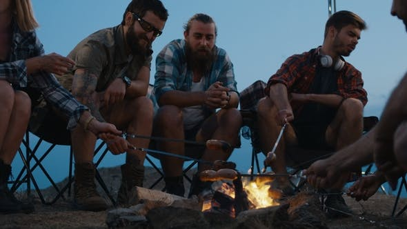 Thumbnail for Friends Frying Sausages on Campfire in Twilight