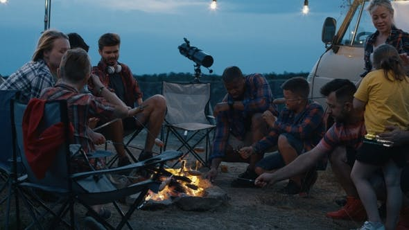 Thumbnail for Group of Traveling Friends Frying Sausages in Campsite