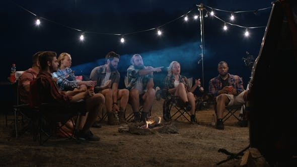 Young People Watching Movies Near Campfire