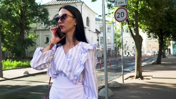 Thumbnail for Stylish Brunette in Sunglasses Standing at Urban Street and Talk on Phone