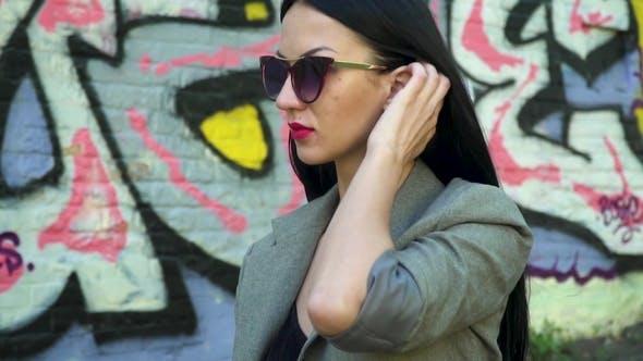 Thumbnail for Stylish Brunette in Sunglasses Straighten Her Hair in