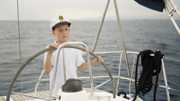 Thumbnail for Little Children Skipper at the Helm Controls of a Sailing Yacht