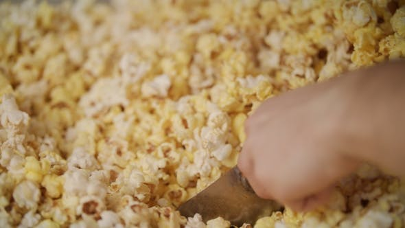Thumbnail for Human Hand Pouring Ready Popcorn From Popcorn Machine By Ladle