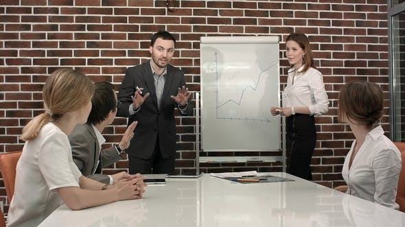 Thumbnail for Business, Education and Office Concept - Serious Business Team with Flip Board in Office Discussing