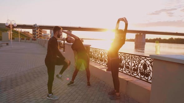 Thumbnail for People Working Out Doing Stretching Against a Beautiful Sunset.
