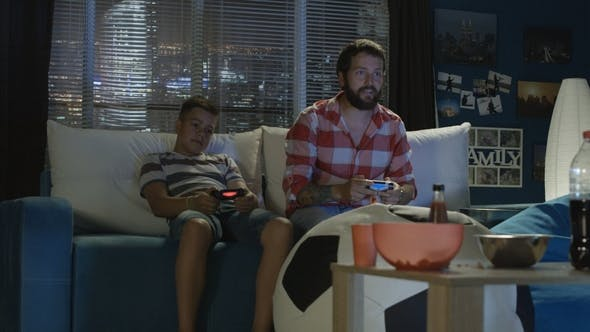 Thumbnail for Man and Boy Playing Videogame Together
