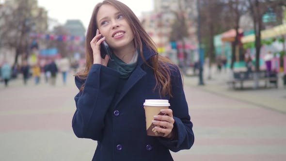 Thumbnail for Dolly Shot of Attractive Mixed Race Girl Talking Smartphone and Drinking Coffee Walks in City Street